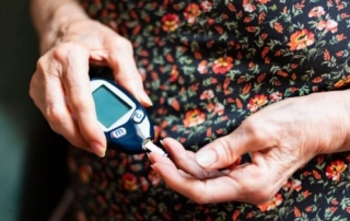 woman measuring her blood glucose levels managing her diabetes